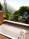 Photograph showing design resort hotel outdoors bathroom beautiful view surrounding hillside forest sunken white bath natural Royalty Free Stock Photography