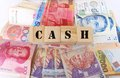 Photograph showing many asian bank notes wooden blocks spelling out word cash upper case letters foreign exchange profit asian Royalty Free Stock Images