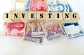 Photograph showing many asian bank notes wooden blocks spelling out word investing upper case letters theme investment asian Stock Image
