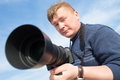 Photographer with big lens under blue sky Royalty Free Stock Image