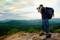 Photographer with big mirror camera on neck and backpack stay on peak of rock. Hilly landscape, fresh green color in valley. Royalty Free Stock Photo