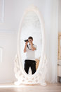 Photographer with the camera in a mirror is reflected Stock Image