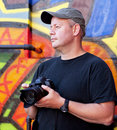 Photographer with camera near graffiti background Stock Photography