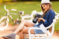 Photographer checking photos on camera happy pretty student sitting at the park her Royalty Free Stock Images