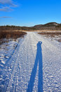 Photographer shadow photographers cast on groomed snowmobile trail Royalty Free Stock Image