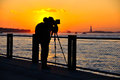 Photographer at sunset a taking picture of the statue of liberty as the sun sets on manhattan new york Royalty Free Stock Photos