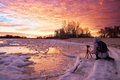 Photographer take pictures on the river bank in winter girl photographed sunset Royalty Free Stock Photos
