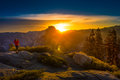 Photographer taking pictures of sunrise yosemite national park g woman at from the glacier point Royalty Free Stock Photo