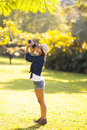 Photographer taking pictures young female outdoors at the park Royalty Free Stock Image