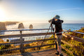 Photographer to the twelve apostles at sunset nature taking pictures with his tripod and wide angle chamber in state of Royalty Free Stock Images