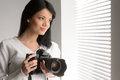 Photography is her hobby portrait of beautiful young woman hold holding a camera and looking through the window Royalty Free Stock Image
