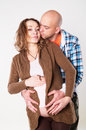 Photography pregnant woman with her husband in the studio in different positions hugging her from behind women on black background Royalty Free Stock Photography