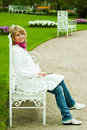 Photos of a blonde girl sitting on a white bench Royalty Free Stock Image