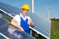 Photovoltaic engineer showing thumbs up at solar panel array energy Stock Image