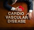 Phrase cardio vascular disease and devastated man made of wooden block letters middle aged caucasian in a black suit sitting at Stock Images
