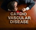 Phrase cardio vascular disease and devastated man made of wooden block letters middle aged caucasian in a black suit sitting at Royalty Free Stock Photo