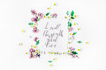 Phrase `Do small things with great love` written in calligraphy style on paper with wreath frame with lilac and chamomile Royalty Free Stock Photo