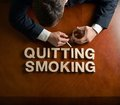 Phrase quitting smoking and devastated man made of wooden block letters middle aged caucasian in a black suit sitting at the table Royalty Free Stock Photo