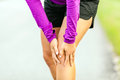 Physical injury running knee pain female runner leg and muscle during outdoors in summer nature sport jogging working out outside Royalty Free Stock Photos