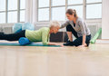 Physical therapist helping elderly woman in her workout senior women exercising with a foam roller being assisted by personal Stock Image