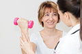 Physical therapy charming mature patient lifts dumbbells with a young therapist Stock Photos
