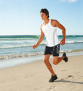 Physically fit man running alone on a beach Royalty Free Stock Photo