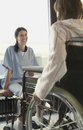 Physician listening to patient in wheelchair young smiling female Stock Photo
