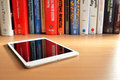 Physics books reflected in ipad mini screen background on the table with retina the foreground on the table Royalty Free Stock Photos