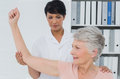 Physiotherapist assisting senior woman to stretch her hand female women in the medical office Royalty Free Stock Photography