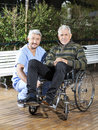 Physiotherapist crouching by senior man in wheelchair at lawn portrait of male men rehab center Stock Image