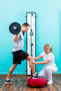 Physiotherapist medicate patient in practice at the physiotherapy doing physical exercises using bar bell Stock Images