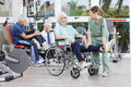 Physiotherapists guiding senior patients to exercise at rehab ce male and female fitness center Stock Image