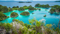 Pianemo islands surrounded by azure clear water and covered by green vegetation. Raja Ampat, West Papua, Indonesia Royalty Free Stock Photo