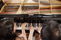 Piano duet two people a couple playing showing mostly their hands Stock Images