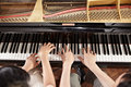 Piano duet two people a couple playing showing mostly their hands Royalty Free Stock Images