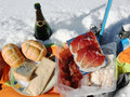 Pic nic on the snow with tipical mountain food sausages and cheeses Stock Photos