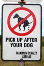Pic up after dog signpost sign board in a park your maximum penalty australian Royalty Free Stock Photo