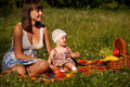 Picinic on the grass young women with her little year old daughter picnic Stock Images