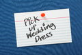 Pick up wedding dress a reminder to written on a white note card and pinned to a blue notice board Stock Photography