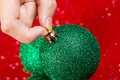 Picking up Green Christmas Ornament Royalty Free Stock Photo