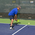 Pickleball action man in blue preparing to hit a backhand dink colorful image of player hitting shot at line near the net Stock Images