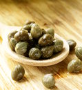 Pickled capers in a wooden spoon Royalty Free Stock Images