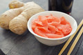 Pickled ginger with soy sauce and wooden chopsticks on plate Stock Image