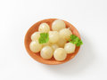 Pickled onions small on terracotta plate Stock Photo