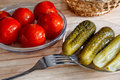 Pickled tomatoes and cucumbers on the table a glass plate wooden Royalty Free Stock Photos