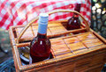 Picnic basket brown wicker with two bottles of wine next to table with a red and white checkered table cloth Royalty Free Stock Photos
