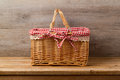 Picnic basket with checked cloth on table Royalty Free Stock Photo