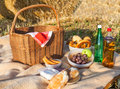 Picnic basket and different food and drinks on straw field hay Royalty Free Stock Photos