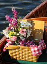 Picnic basket with flowers - on a wooden boat Royalty Free Stock Image