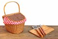Picnic basket and grill tools on the outdoor table isolated bbq wood white background Royalty Free Stock Photography